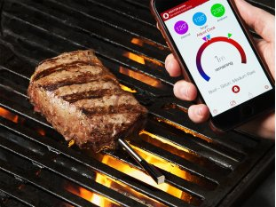 Wireless meat thermometer in a steak and a phone showing the temperature