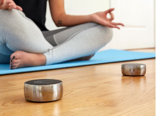 person on yoga mat with meditation speakers