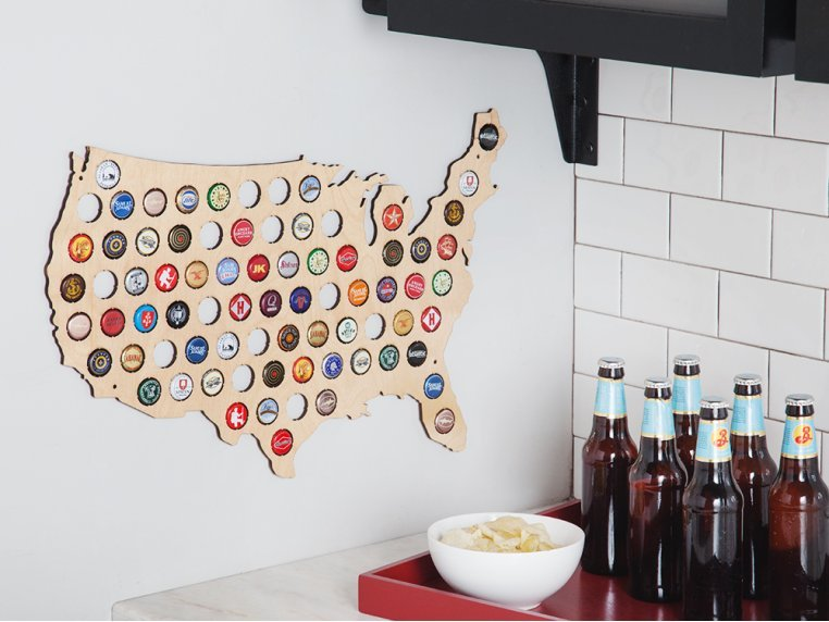 Bottle caps from different breweries sit in a wood map of the United States from Torched Products